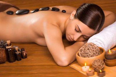 une jolie femme se fait masser au pierres chaudes