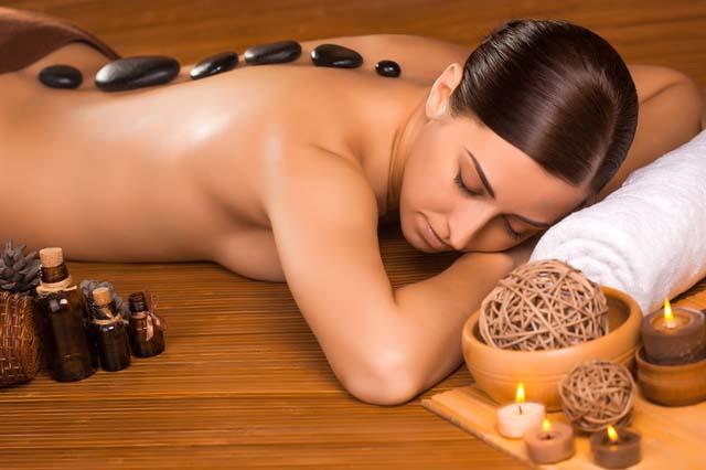 jolie femme se fait masser au pierres chaudes